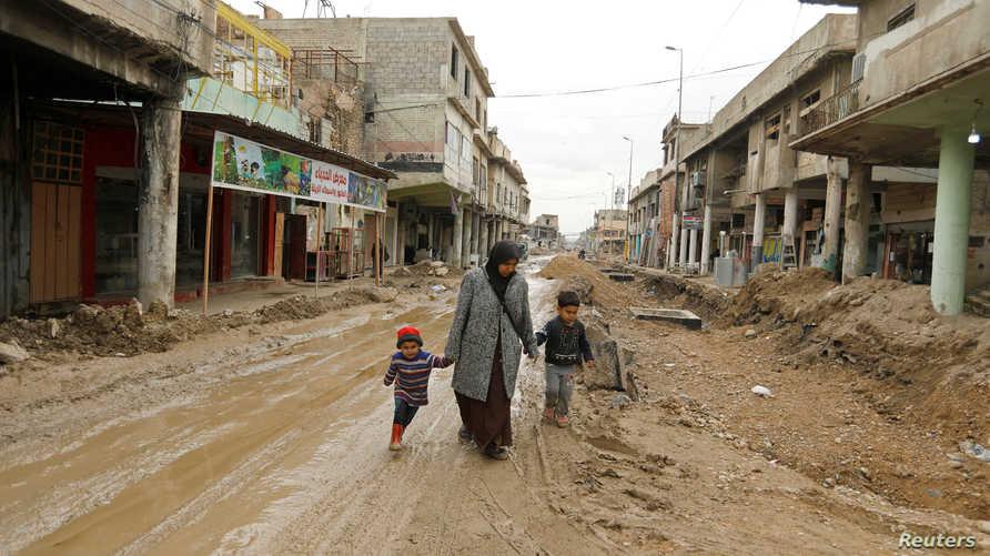 عراقية مع ولديها في المدينة القديمة في الموصل