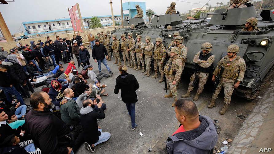 محتجون وعناصر في الجيش اللبناني على إحدى الطرقات المؤدية إلى المدخل الجنوبي لمدينة طرابلس