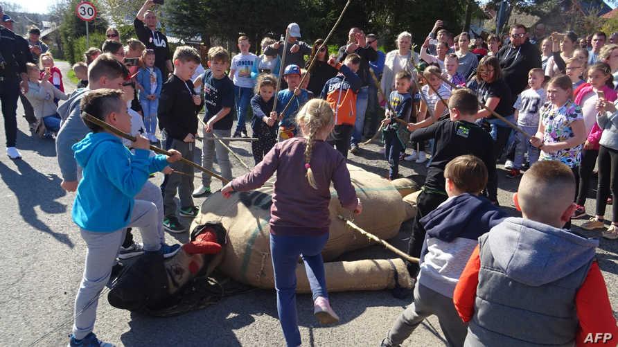 أطفال يضربون بالعصي دمية من المفترض أنها تمثل يهوذا في بلدة بروتشينك في بولندا