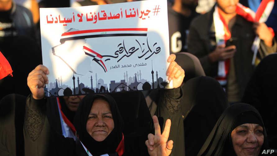 """مناصرة للتيار الصدري ترفع لافتة تقول """"جيراننا أصدقاؤنا لا أسيادنا"""""""