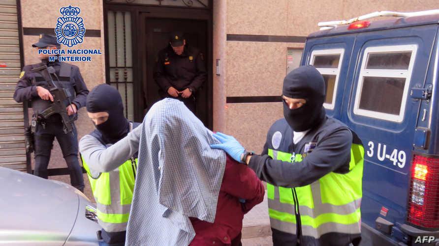 عنصران في الشرطة الإسبانية مع أحد المعتقلين