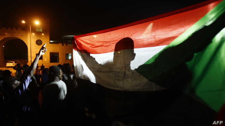 متظاهر يحمل علم السودان خلال اعتصام امام مقر القيادة العامة في 30 أيار/مايو