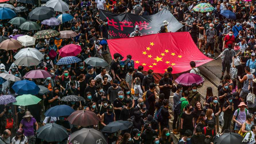 متظاهرون في هونغ كونغ يحملون علم الصين ووضعت فيه النجوم على شكل علامة الصليب المعقوف النازية