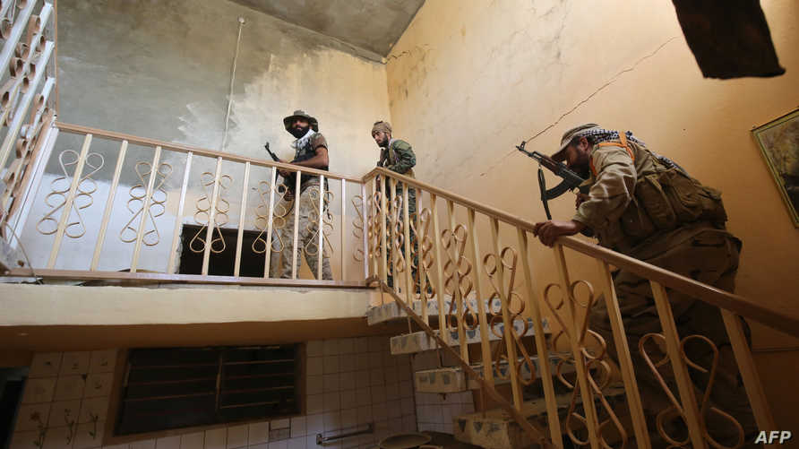 عناصر في القوات العراقية داخل أحد المباني في قرية الشهابي شرق الفلوجة