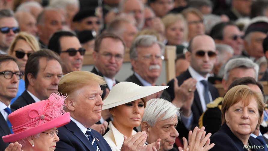 ترامب وميركل خلال احتفالات ذكرى إنزال النورماندي