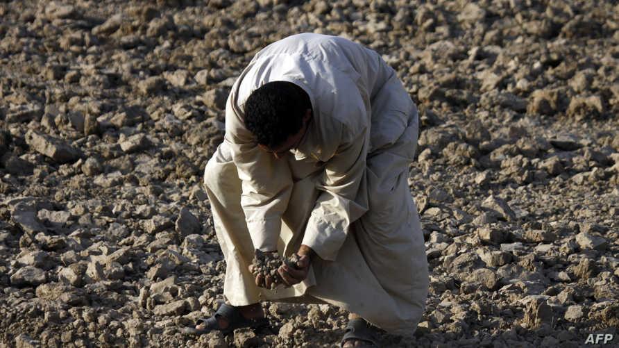 عراقي يتفحص أرضه في ظل موجة الجفاف التي تضرب مناطق عراقية