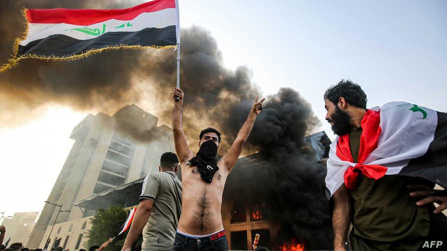 متظاهر يرفع العلم العراقي في ساحة التحرير وسط بغداد