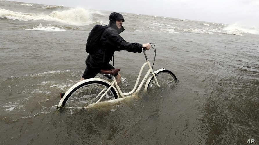 مواطن أميركي يحاول أن يجر دراجته الهوائية فيما تدفع الريح مياه البحيرة لتصد طريقه في مانديفيل بولاية لويزيانا