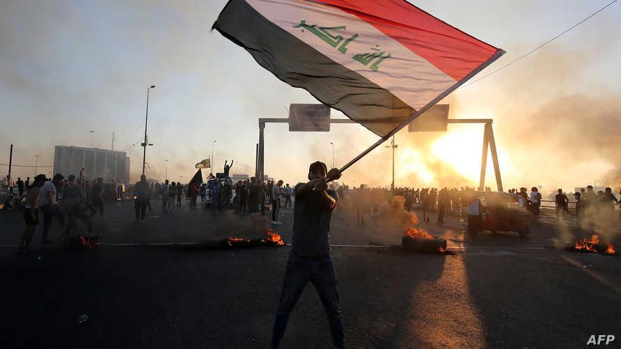 متظاهر يحمل العلم العراقي خلال اليوم الخامس من سلسلة الاحتجاجات التي شهدتها المدن العراقية لمناهضة الفساد والمطالبة باستقالة الحكومة