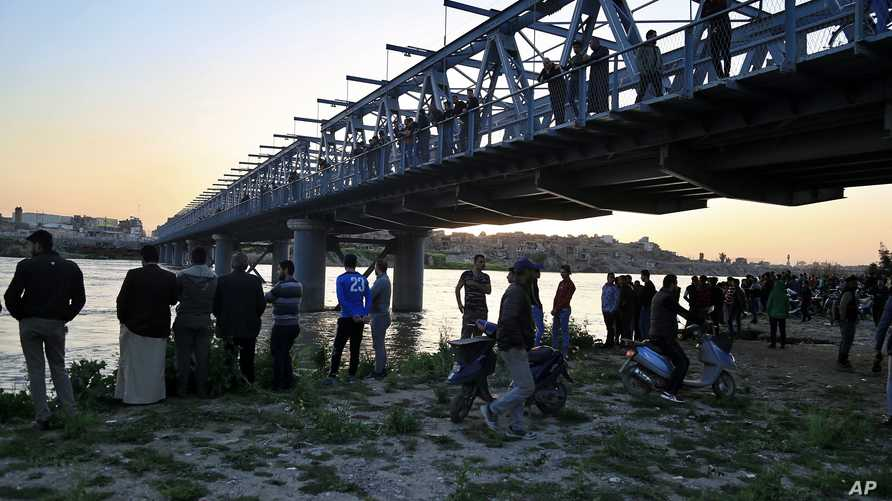 سكان وأهالي ضحايا على ضفة دجلة في الموصل بعد غرق العبارة