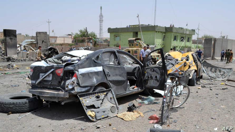 عراقيون يتفقدون موقع الهجومين اللذين استهدفا نقطة التفتيش التابعة للشرطة في قضاء طوزخرماتو