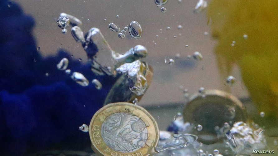 قطع نقدية من الجنيه الاسترليني بين ألوان مائية لعلم الاتحاد الأوروبي-تعبيرية