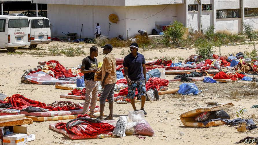 مهاجرون خارج مركز الاحتجاز الذي تعرض للقصف في تاجوراء