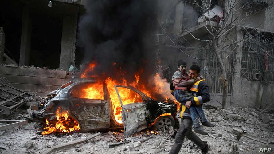 مواطن يحاول إنقاذ طفل من القصف الذي استهدف الغوطة الشرقية في بداية العام 2018