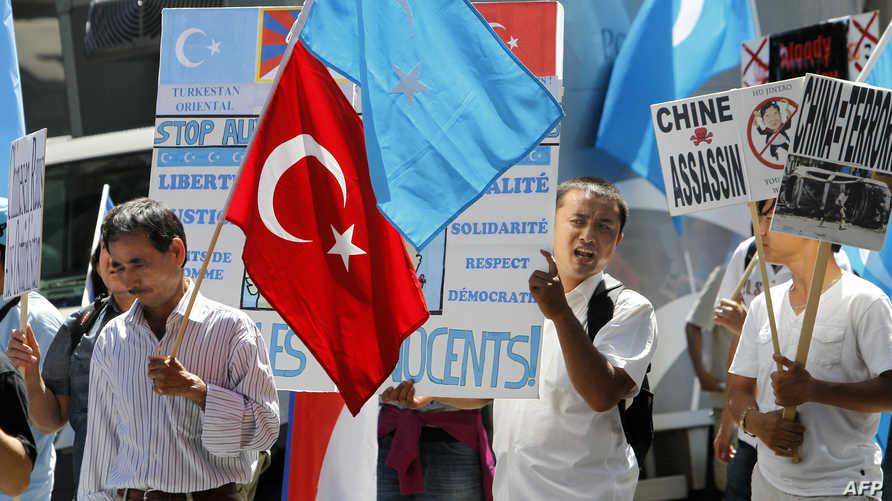 محتجون أيغور يلوحون بأعلامهم والعلم التركي في مظاهرة بباريس - أرشيف