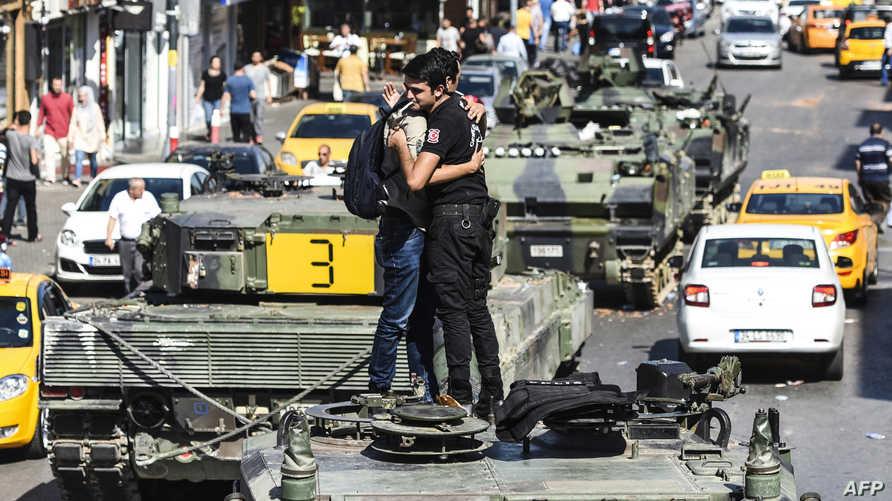 شرطي تركي يحتضن أحد المواطنين على متن دبابة