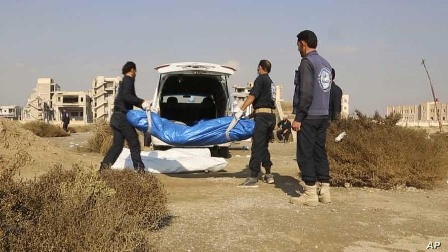 عمال سوريون يحملوث جثة تم انتشالها من مقبرة جماعية في الرقة