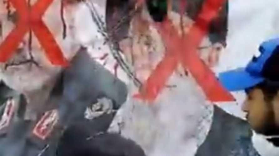 محتجون عراقيون يضربون صورة لخامنئي وسليماني فيساحة التحرير في بغداد