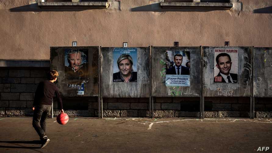 طفل يلعب بجانب لوحات إعلانية لعدد من مرشحي  الانتخابات الرئاسية في فرنسا