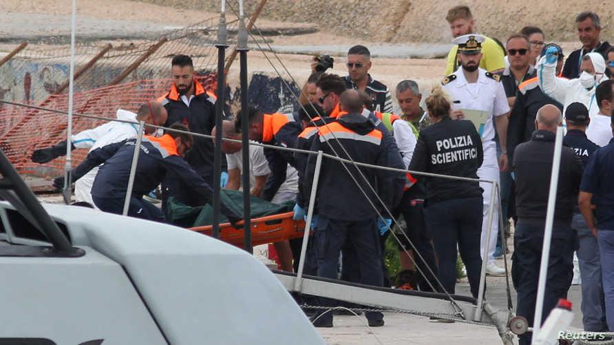 مسعفون ينقلون حمالة من على متن سفينة إنقاذ بعد غرق زورق يحمل حوالي 50 مهاجرا قبالة لامبيدوزا الإيطالية