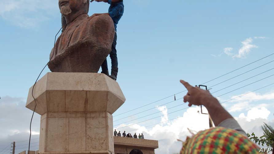 تحطيم تمثال حافظ الأسد في إحدى البلدات الكردية شمال سورية عام 2012 (أرشيف)
