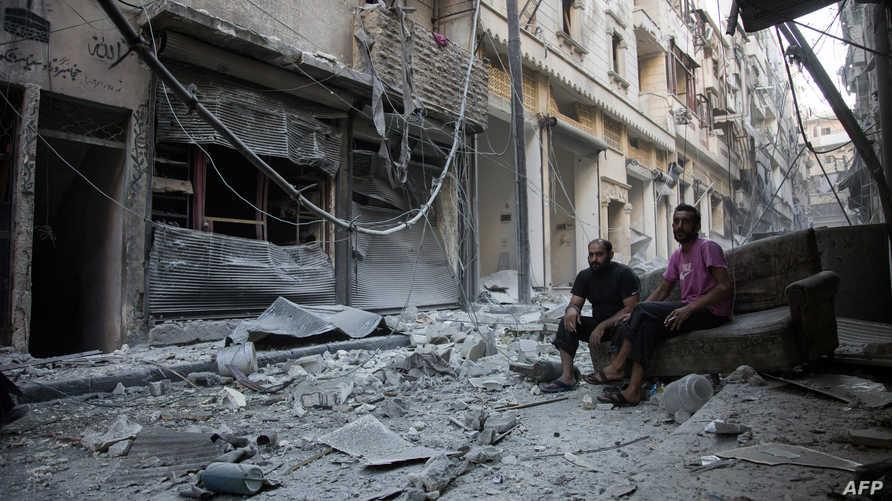 سوريان يجلسان بين الأنقاض في حلب