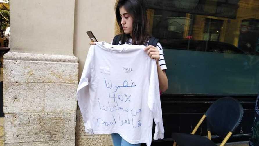 فتاة المطعم تقف وحيدة احتجاجا على قرار الإدارة تخفيض الرواتب قبل أن يتضامن معها العشرات