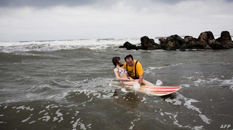سينجي ناكاجيما يركب الأمواج مع الدمية ساوري (أرشيف)
