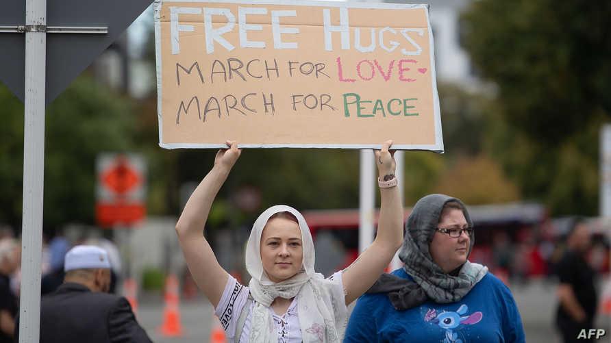 ترفع لافتة تعلن فيها تقديم عناق مجاني وتدعو للسلام والحب