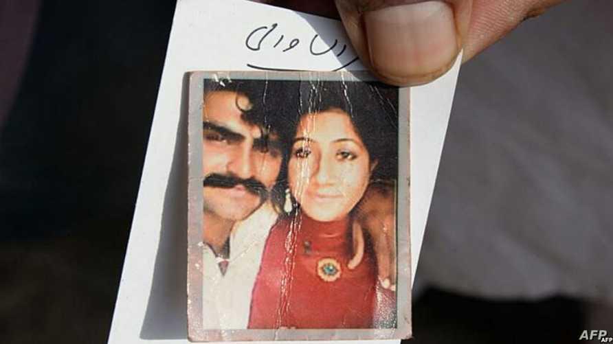 باكستاني يحمل صورة زوجته التي قتلت الجمعة بدعوى الشرف