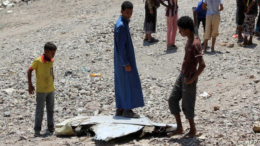 أطفال يمنيون يقفون إلى جانب ما قال سكان محليون إنها قطعة من حطام مقاتلة إماراتية سقطت في آذار/ مارس الماضي في عدن (أرشيف)