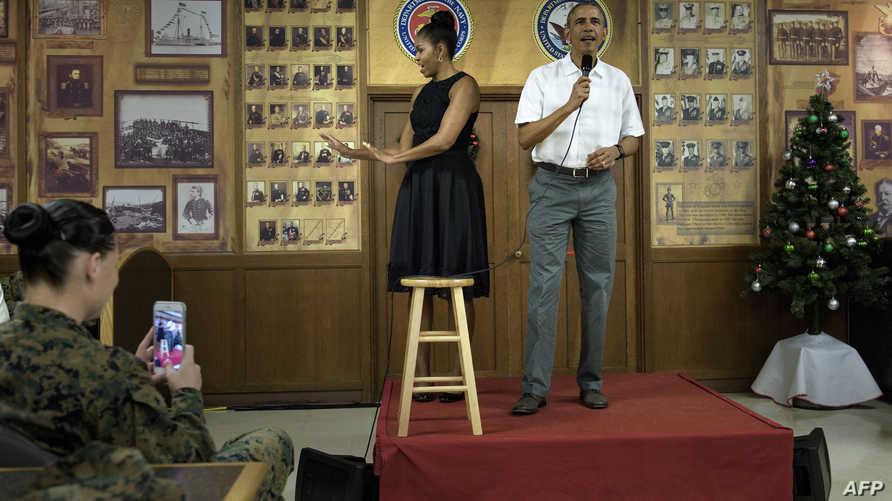 الرئيس أوباما خلال كلمته أمام جنود القاعدة البحرية وإلى جانبه السيدة الأولى ميشيل أوباما