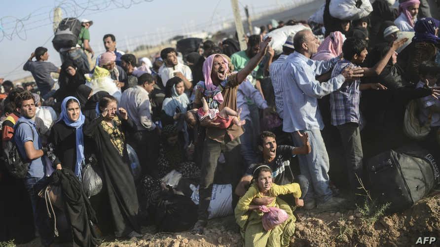 لاجئون سوريون يحاولون عبور حاجز حدودي بين سورية وتركيا- أرشيف