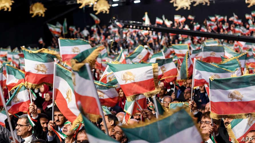 معارضون إيرانيون يحملون العلام الإيراني السابق في مؤتمر للمعارضة الإيرانية - 13 يوليو 2019