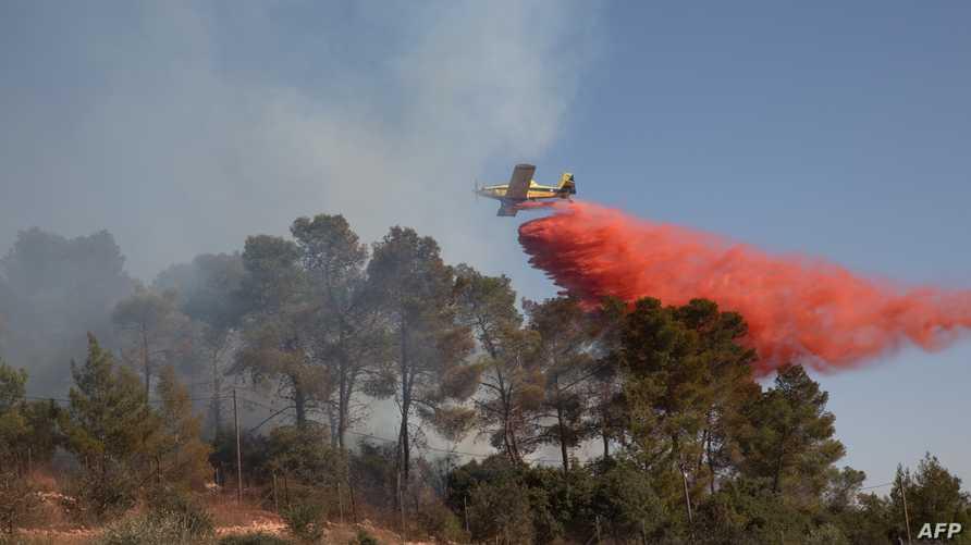طائرة إسرائيلة تخمد النيران المشتعلة