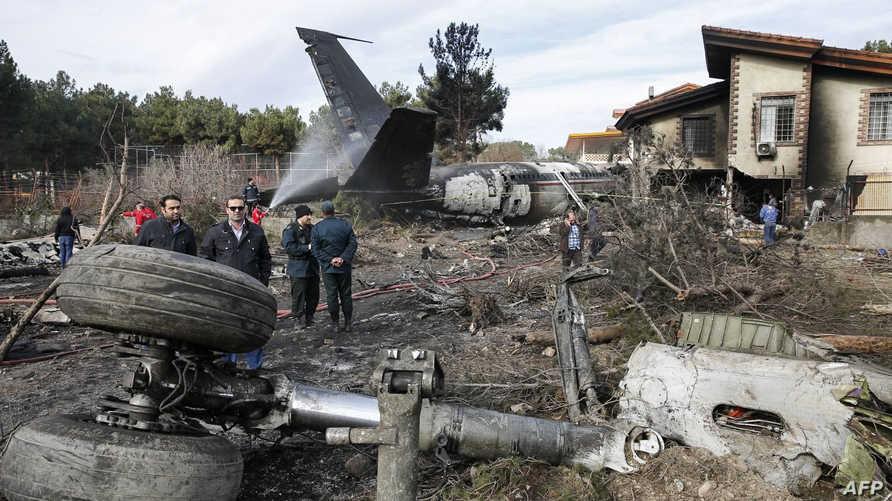 إيرانيون يتجمعون حول حطام طائرة الشحن الإيرانية التي تحطمت بالقرب من العاصمة طهران