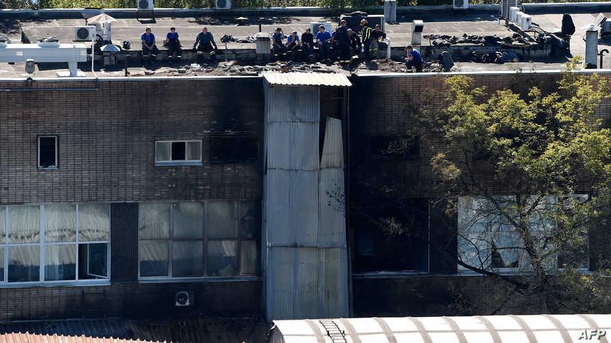 عمال الإنقاذ فوق سطح المطبعة التي اندلع فيه الحريق
