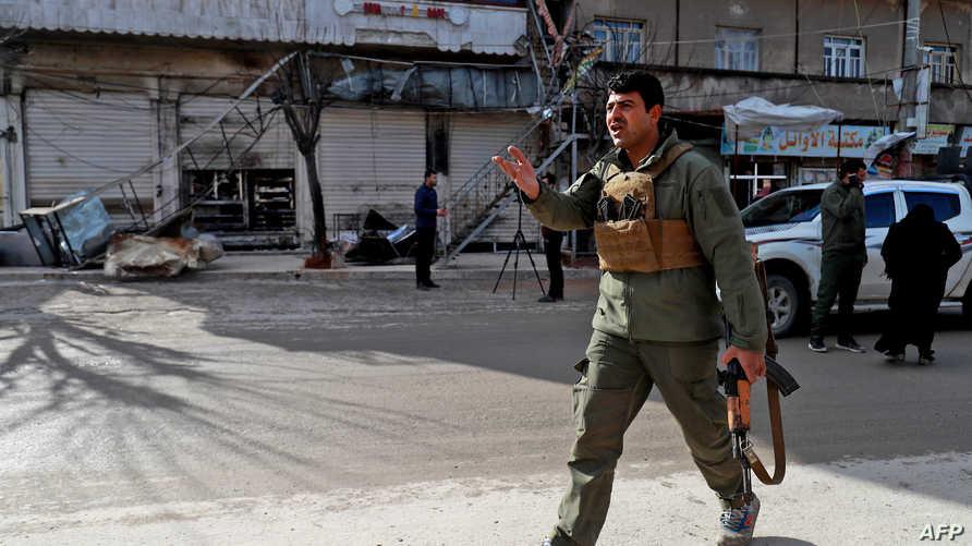 أحد عناصر قوات الأمن المحلية في منبج أمام المطعم الذي استهدفه الهجوم الانتحاري