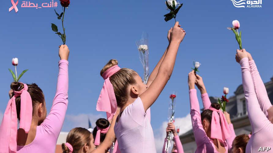 فتيات يؤدين رقصة أمام المسرح الوطني في كوسوفو كجزء من حملة التوعية حول سرطان الثدي