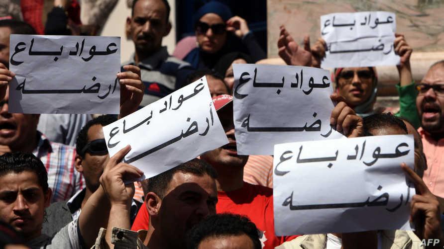 """مصريون يرفعون عبارة """"عواد باع أرضه"""" للتنديد بمنح جزيرتي تيران وصنافير للسعودية."""