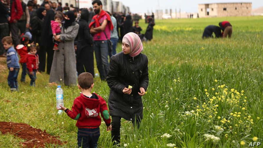 فتاة سورية تقطف وردة، قد تكون الأخيرة في بلدتها، قد مغادرتها وآخرين من دوما إلى الشمال السوري، في اتفاق بين النظام السوري والمعارضة بعد حصار طويل لدوما