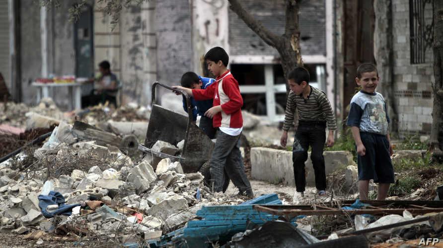 أطفال في إحدى المناطق المدمرة بمدينة حمص- أرشيف