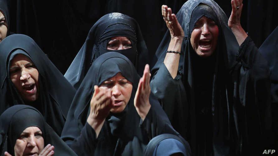 نساء يؤدين طقوسا دينية في كربلاء
