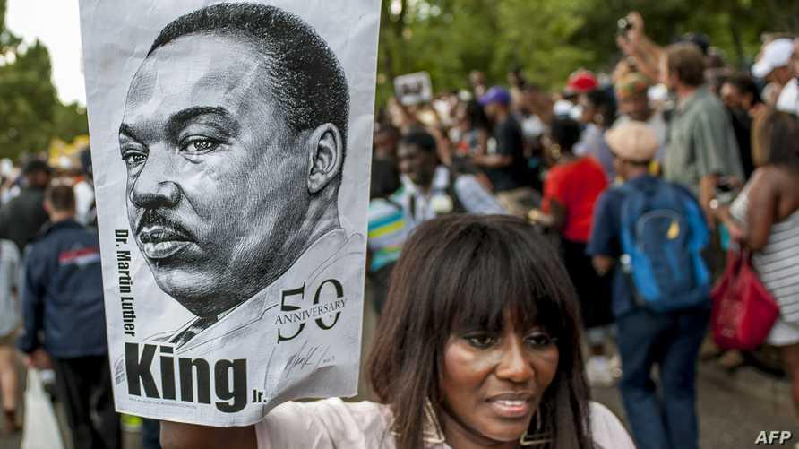 مواطنة أميركية تحتفل بذكرى مسيرة لوثر كينغ في واشنطن