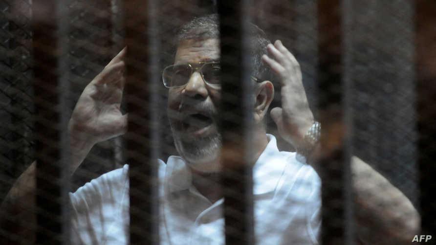 محمد مرسي خلال إحدى جلسات محاكمته-أرشيف