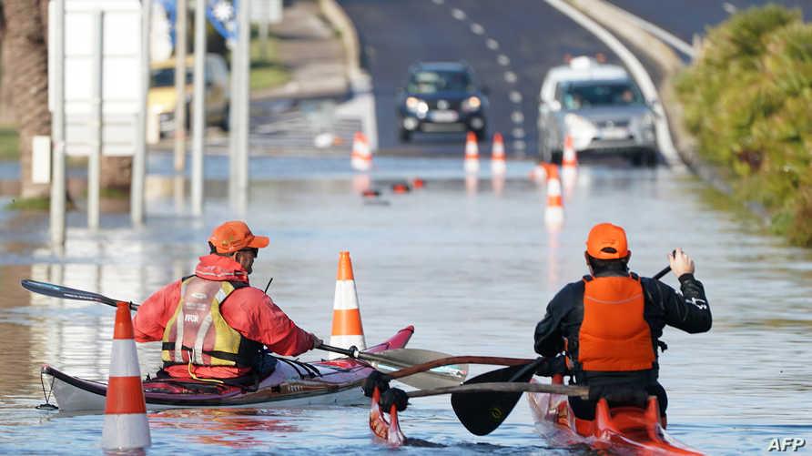 رجلان يجدفان بزورقيهما في طريق غارق بمياه الأمطار جنوبي فرنسا، السبت