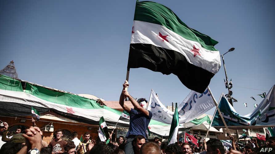 يحمل علم المعارضة السورية في تظاهرة في إدلب قبل أيام