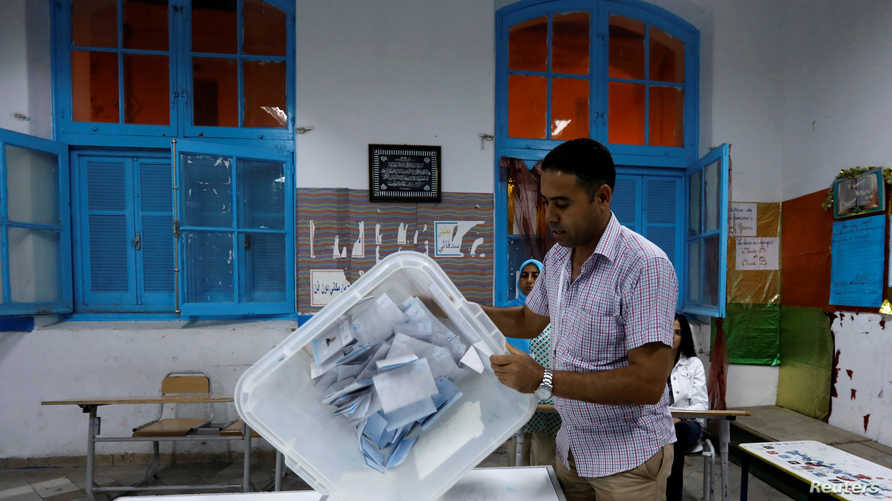 مشرف على الانتخابات يفرّغ الأصوات بعد إغلاق صناديق الاقتراع للانتخابات الرئاسية التونسية في 13 أكتوبر 2019