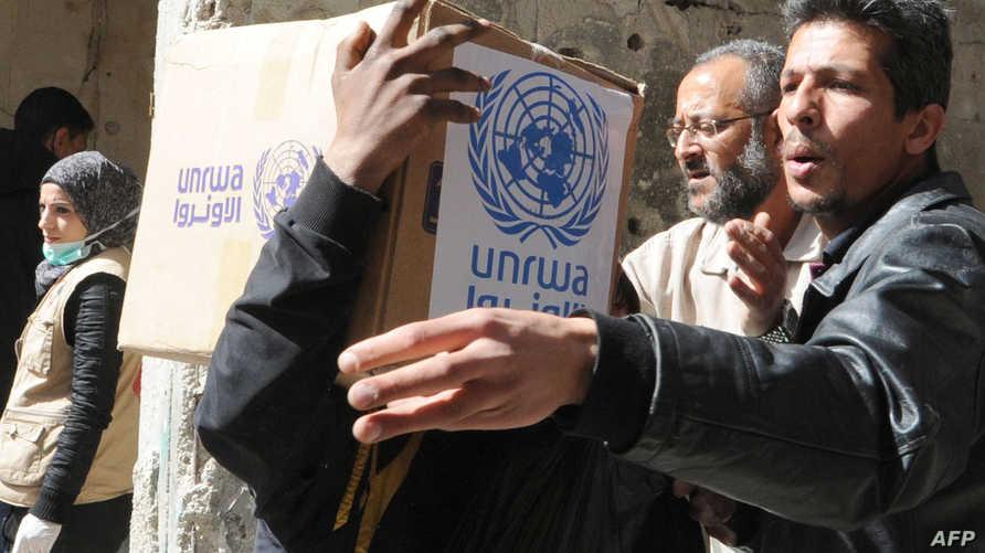"""سكان يحملون مساعدات تقدمه """"أنروا"""" في مخيم اليرموك"""