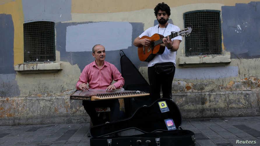 لاجئان سوريان يعزفان في أحد شوارع اسطنبول